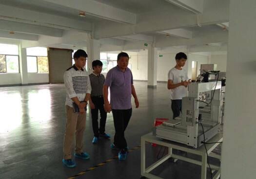 日月辉曾总(右前)与中心工作人员(左后)参观公司设备.jpg